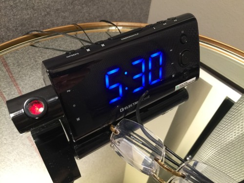 Well, you've got to wake up first and take a look at your alarm clock. Reading any clock is so simple. Right? But not so easy if you can't read the digits without your glasses. The solution… How about a projection clock for your ceiling?