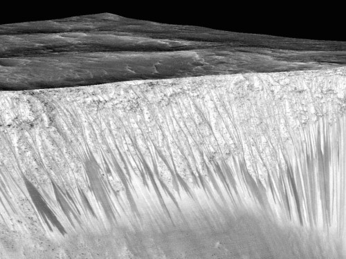 The walls of the Garni Crater on Mars have dark, narrow streaks that NASA says reveal liquid water. Terran scientists are jumping up and down with glee, but there's a catch…